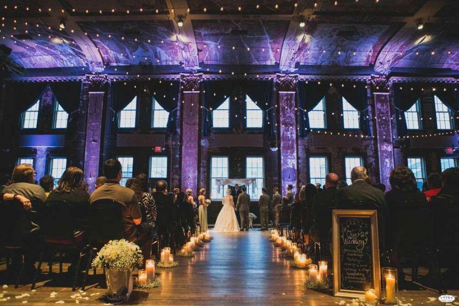 Gorgeous Wedding Ceremony with dramatic up-lighting, candles running down the aisle and lights strung across ceiling