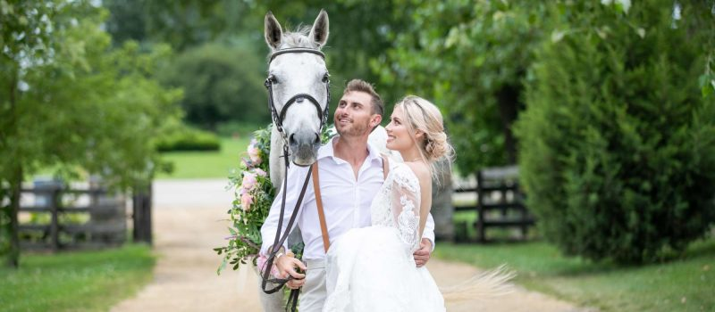 Bride and groom with white horse
