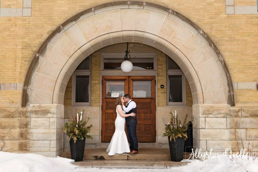Couple embrace under arch at vintage building- Allysha Noelle Photography