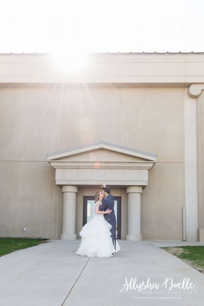 Bride and groom embrace with sun shining a spotlight on them-Allysha Noelle Photography