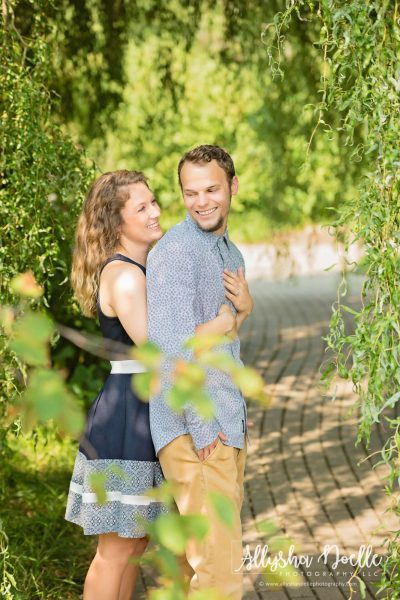 Couple pose for engagement picture on garden path