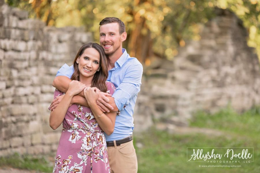 couple pose for engagement photo near old stone wall-Allysha Noelle Photography