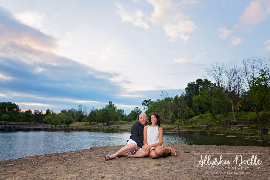 couple pose on beach by Wisconsin lake for their engagement photos