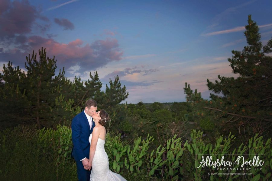 bride and groom kiss in wooded setting- Allysha Noelle Photography