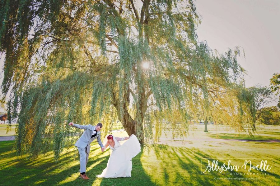 Bride and groom under sunlit willow tree- Allysha Noelle Photography