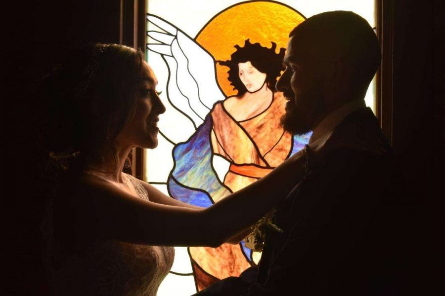 Bride & Groom with stained glass window at the Kettle Moraine Ranch chapel