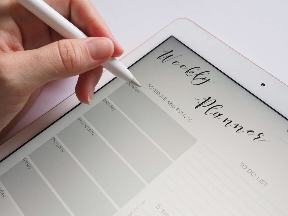 person holding stylus white tablet planner