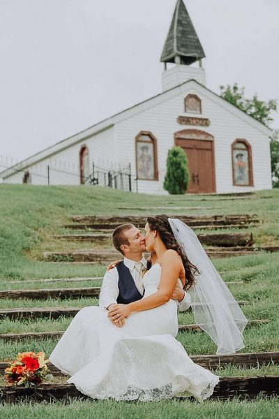 bride sits on grooms lap outside of Kettle Moraine Ranch Chapel