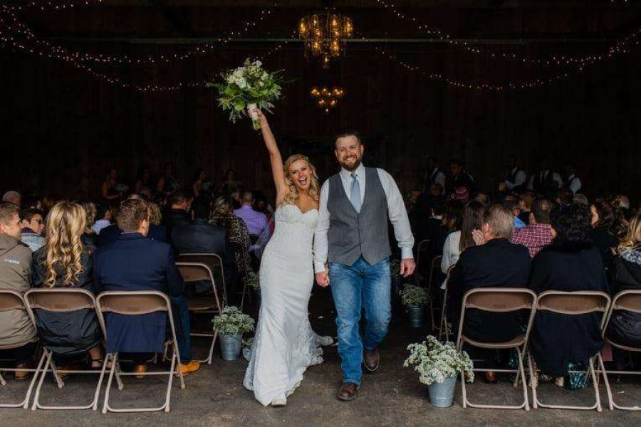 Bride raises bouquet as she and groom come back up the aisle