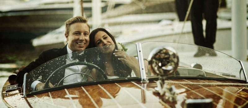 bride and groom on old fashioned wooden speed boat in Lake Geneva