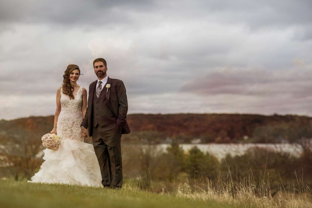 bride and groom standing on a hill in Lake Geneva