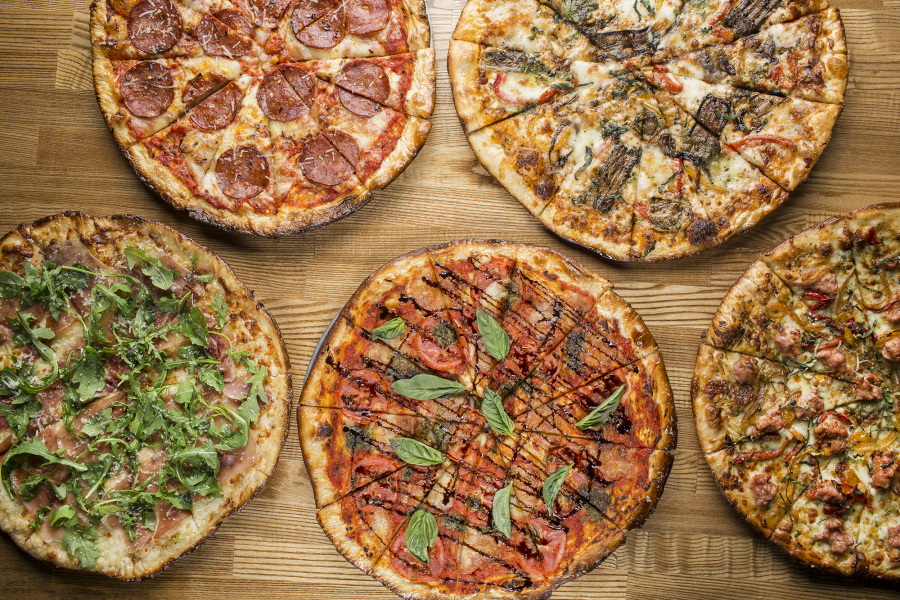 Pizzas displayed on wood counter