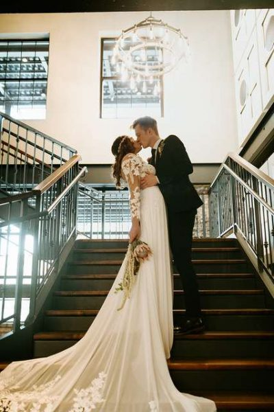 Bride and groom on the grand staircase at the Gage