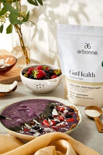 Bowl of berries with a pouch of Arbonne Gut Health Probiotics next to it.