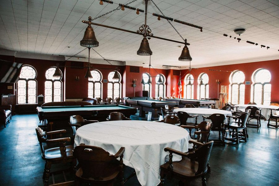 Tables surrounding pool tables and decorative windows