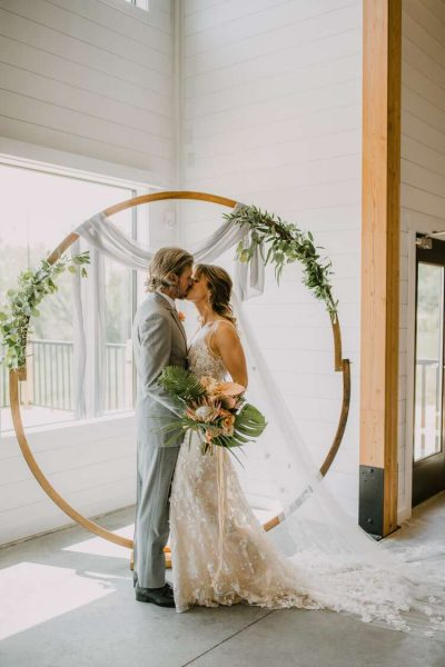 Bride and groom kiss by modern floral arch - Image by DeGroot Film Co.