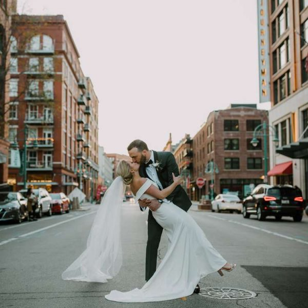 Groom dips and kisses bride on downtown Milwaukee street- Image by DeGroot Film Co.