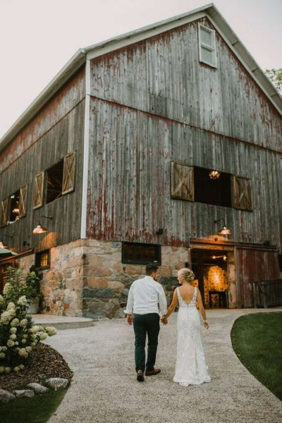 Bride and groom walk hand in hand towards rustic barn venue- Image by DeGroot Film Co.