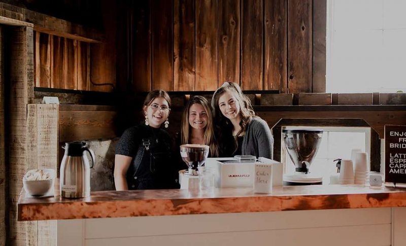 3 baristas stand behind coffee bar-available for Milwaukee area weddings