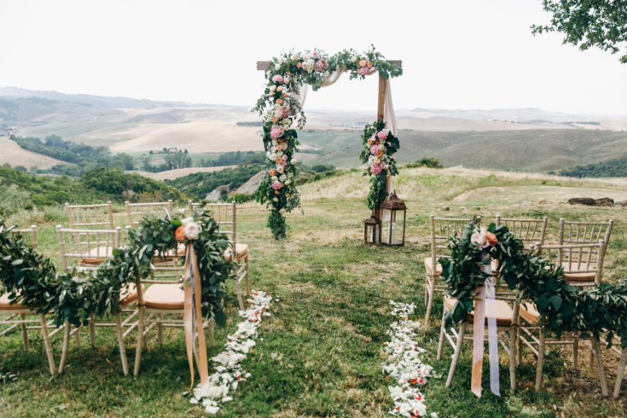 Simple wooden ceremony arch draped with lush fresh flowers