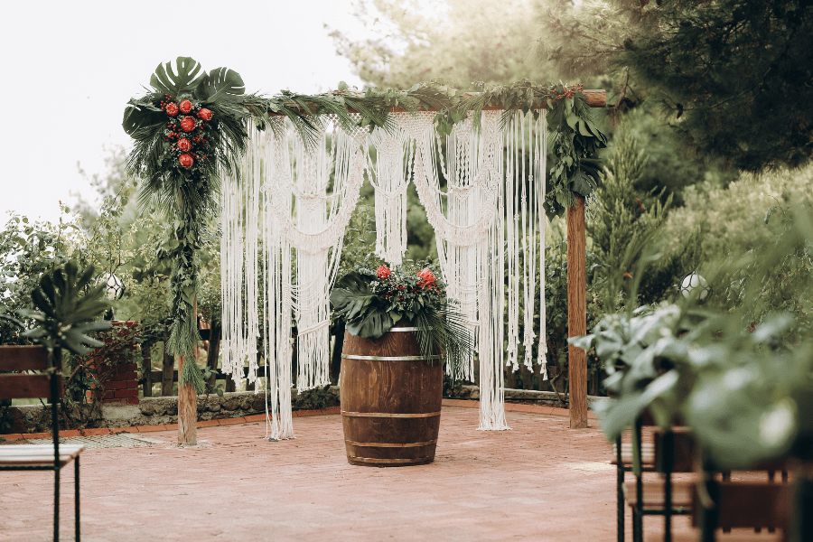 Macramé curtains with tropical floral and greenery accents create this wedding backdrop