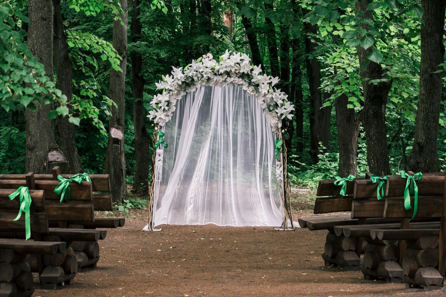 Wedding ceremony set up in a wooded area with white sheer curtains and floral arch