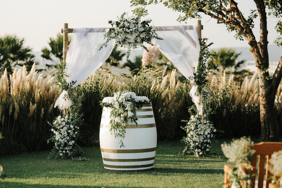 Wedding arch with sheer white curtains and lush white floral accents
