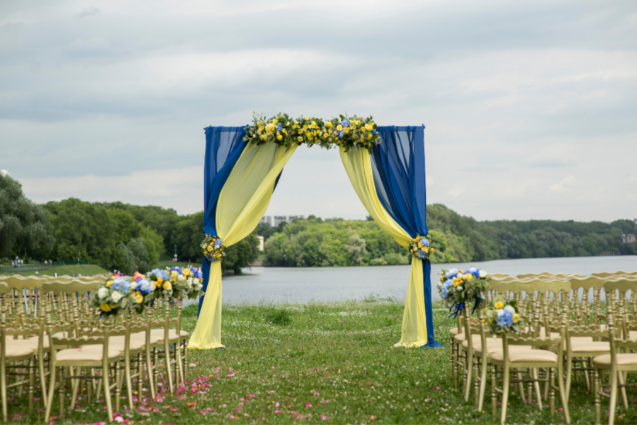 Bright blue and yellow curtains and florals enhance this lakeside wedding arch.