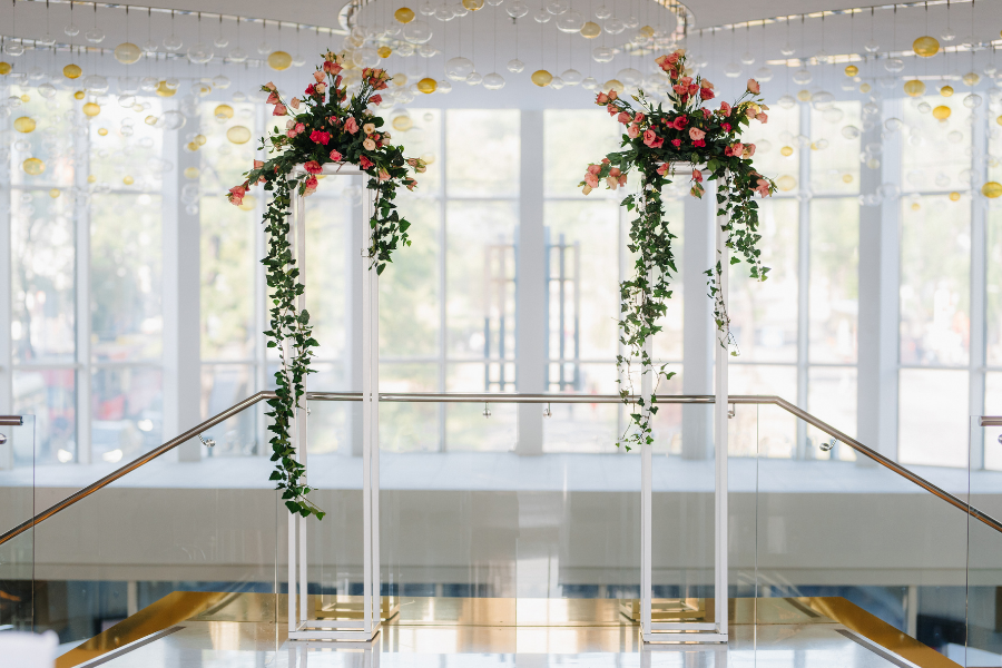 Clear acrylic pillars topped with vibrant floral arrangements